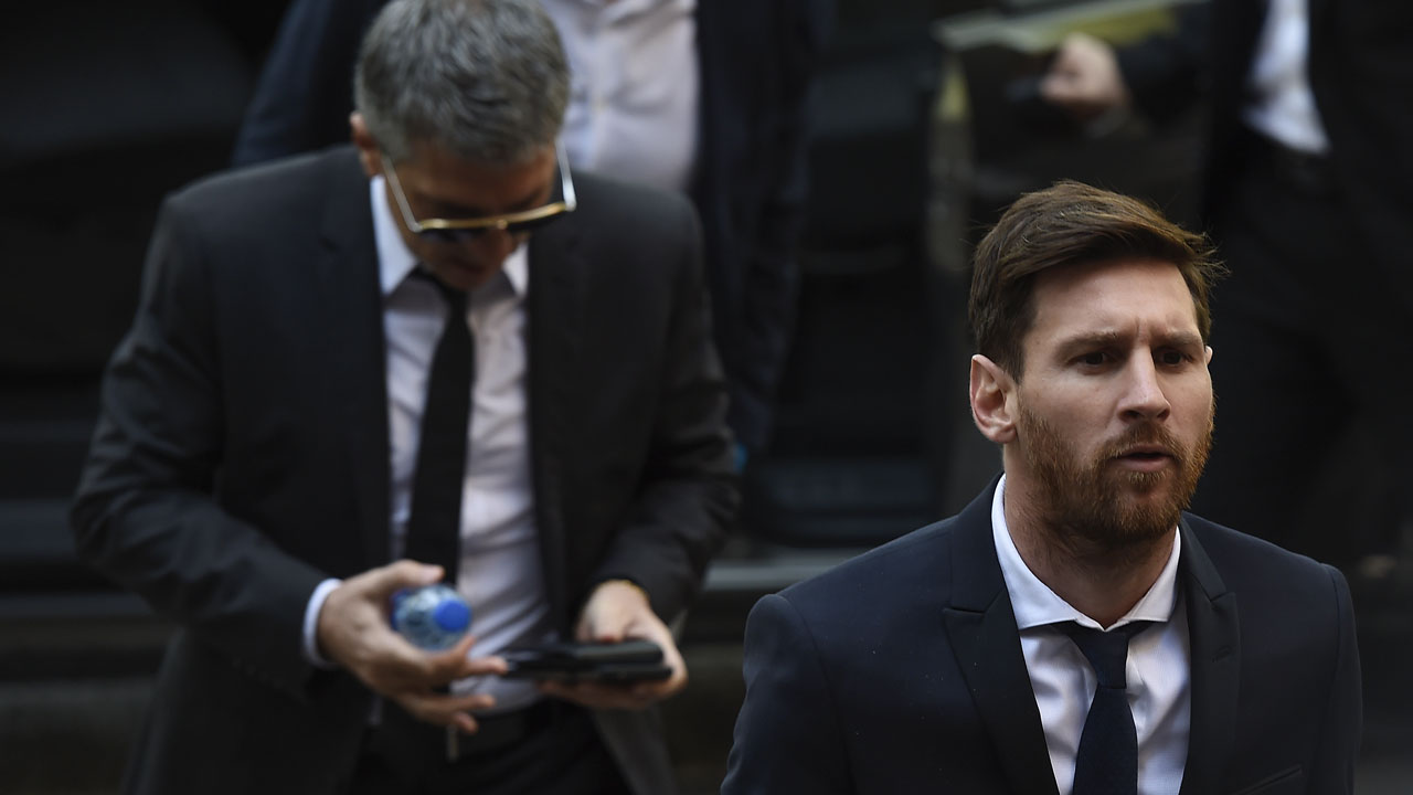 Barcelona's football star Lionel Messi (R) followed by his father Jorge Horacio Messi arrives at the courhouse on June 2, 2016 in Barcelona, where Messi and his father are to face judges in a tax fraud case. The 28-year-old football star was cheered and jeered as he emerged from a van accompanied by his father Jorge Horacio Messi. The two are accused of using a chain of fake companies in Belize and Uruguay to avoid paying taxes on 4.16 million euros ($4.6 million) of Messi's income earned through the sale of his image rights from 2007-09. / AFP PHOTO / JOSEP LAGO