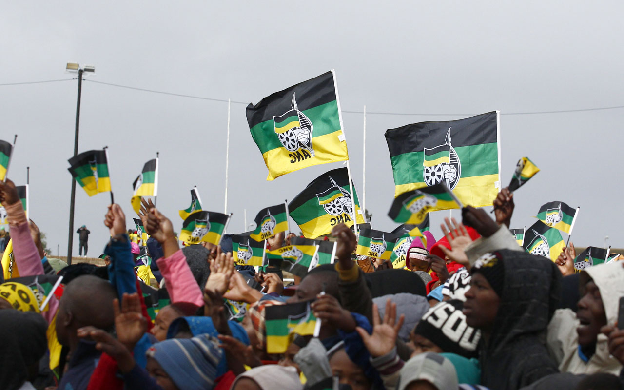 People wave flags of the  African National Congress (ANC) as they attend a rally of the party at the Dan Qeqe stadium in Port Elizabeth, on July 23, 2016 ahead of the municipal elections on August 3.  / AFP PHOTO / MICHAEL SHEEHAN