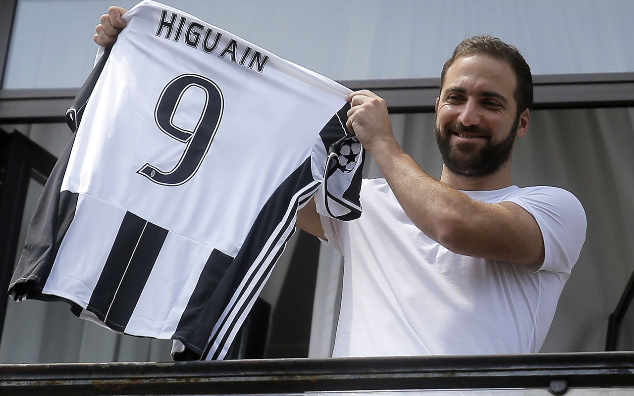 Juventus' forward Gonzalo Higuain from Argentina holds his jersey at the Juventus' headquarter in Turin on July 27, 2016. Gonzalo Higuain completed a sensational move to Juventus after the Italian champions agreed to pay a 90 million euros ($98.8m) fee, the third highest in history, to wrest the Argentine striker from Napoli on July 26. In what is the biggest ever transfer fee recorded between two Serie A clubs, Higuain's move to Turin on a five-year deal was confirmed by Juventus two hours after being published by Serie A league bosses on their official website.  / AFP PHOTO / MARCO BERTORELLO