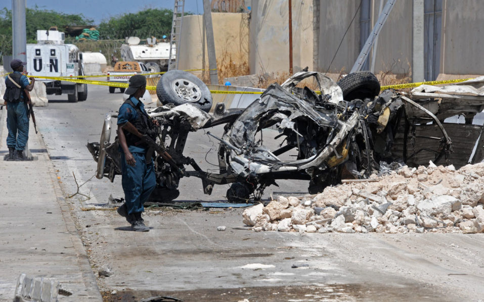 Somali soldiers pass near the wreckage of a car bomb outside the UN's office in Mogadishu on July 26, 2016. At least 13 people were killed on July 26 in twin bombings near UN and African Union buildings adjoining Mogadishu's airport, police said, in what the jihadist Shabaab group claimed as a suicide attack. / AFP PHOTO / MOHAMED ABDIWAHAB