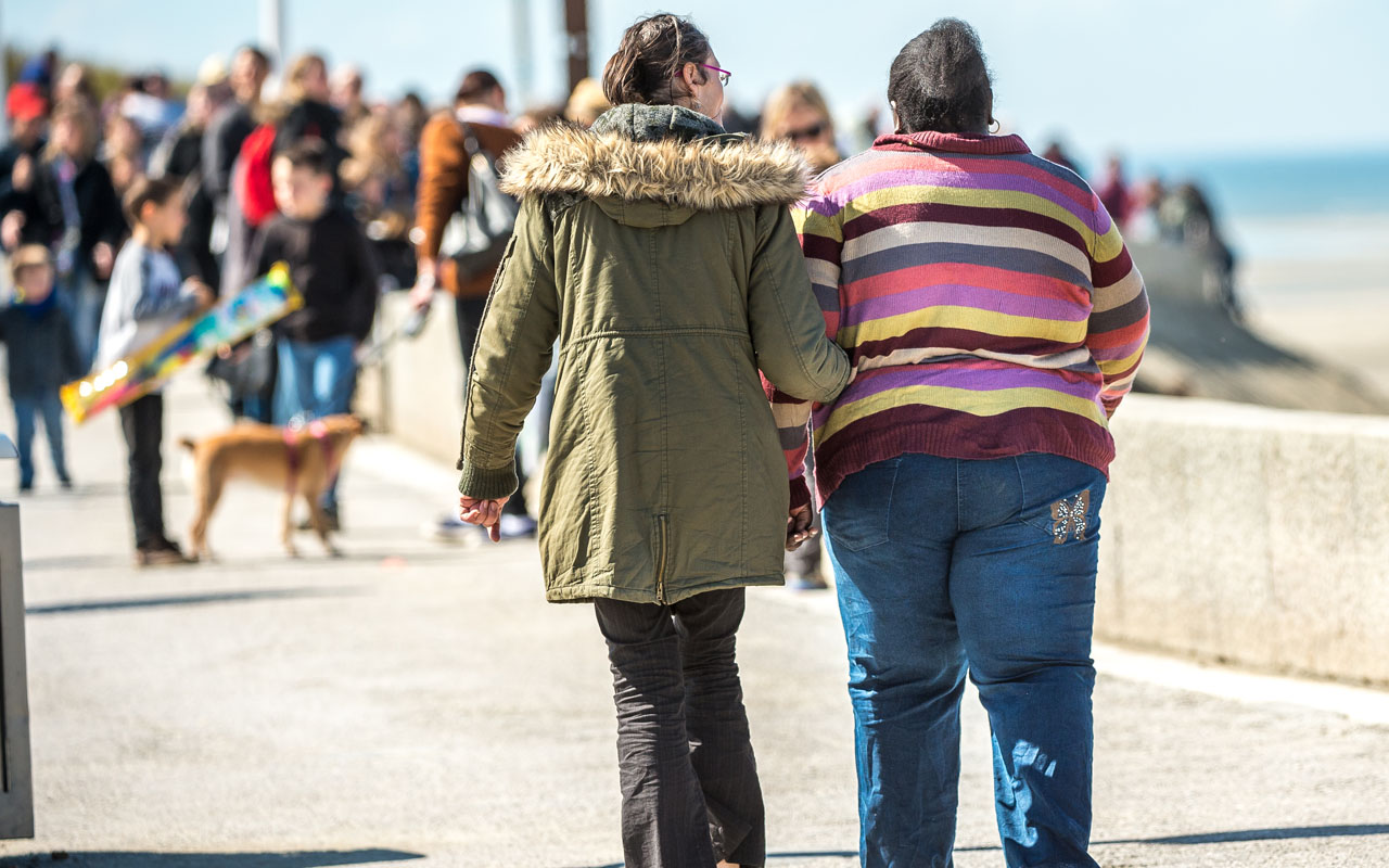 (FILES) This file photo taken on April 12, 2016 shows a woman walking with an overweight person in Berck-sur-Mer, northern France. Being overweight shaves about a year off a person's life expectancy, a heavy price which soars to about 10 years for the severely obese, a large-scale study said on July 14, 2016. / AFP PHOTO / PHILIPPE HUGUEN