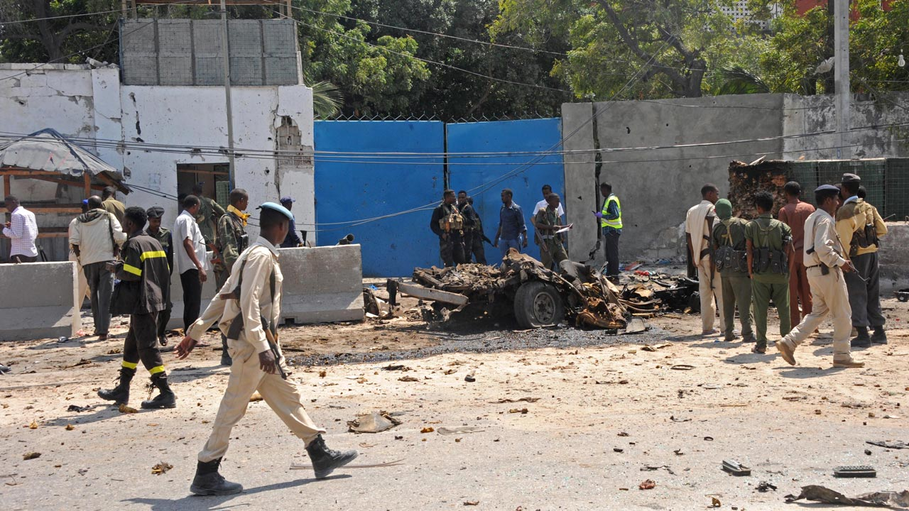 Military and police gather at the scene of a suicide attack in Mogadishu, on July , 31, 2016. Six people were killed in a gun and car-bomb assault on a police building in the centre of the Somali capital that also left seven assailants dead, Security Minister Abdirasak Omar Mohamed said. That attack was claimed by Al-Qaeda-linked Shabaab militants fighting to overthrow Somalia's internationally-backed government. Mohamed ABDIWAHAB / AFP