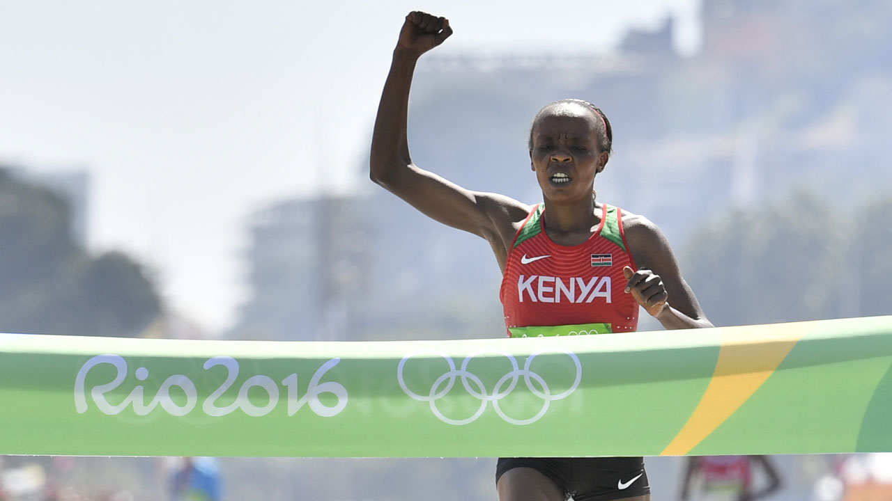 Kenya's Jemima Jelagat Sumgong celebrates her victory as she crosses the finish line of the Women's Marathon during the athletics event at the Rio 2016 Olympic Games at Sambodromo in Rio de Janeiro on August 14, 2016. FABRICE COFFRINI / AFP