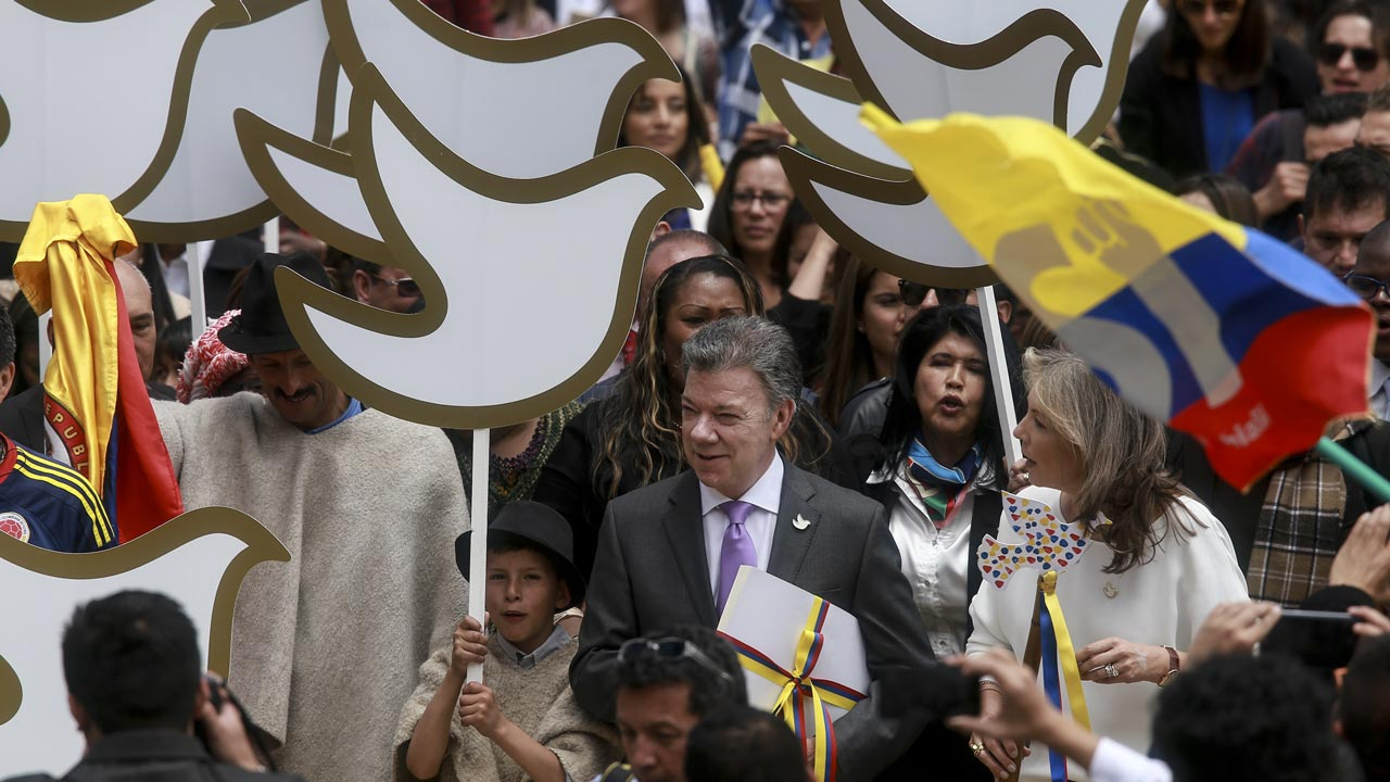 Colombian President Juan Manuel Santos (C) carries a copy with the final text of the peace agreement with the Revolutionary Armed Forces of Colombia (FARC) guerrillas, on his way from the presidential palace to the National Congress in Bogota on August 25, 2016. Colombian President Juan Manuel Santos ordered the army Thursday to observe a definitive ceasefire with the FARC rebels after the two sides reached a deal to end their half-century conflict. IVAN VALENCIA / AFP