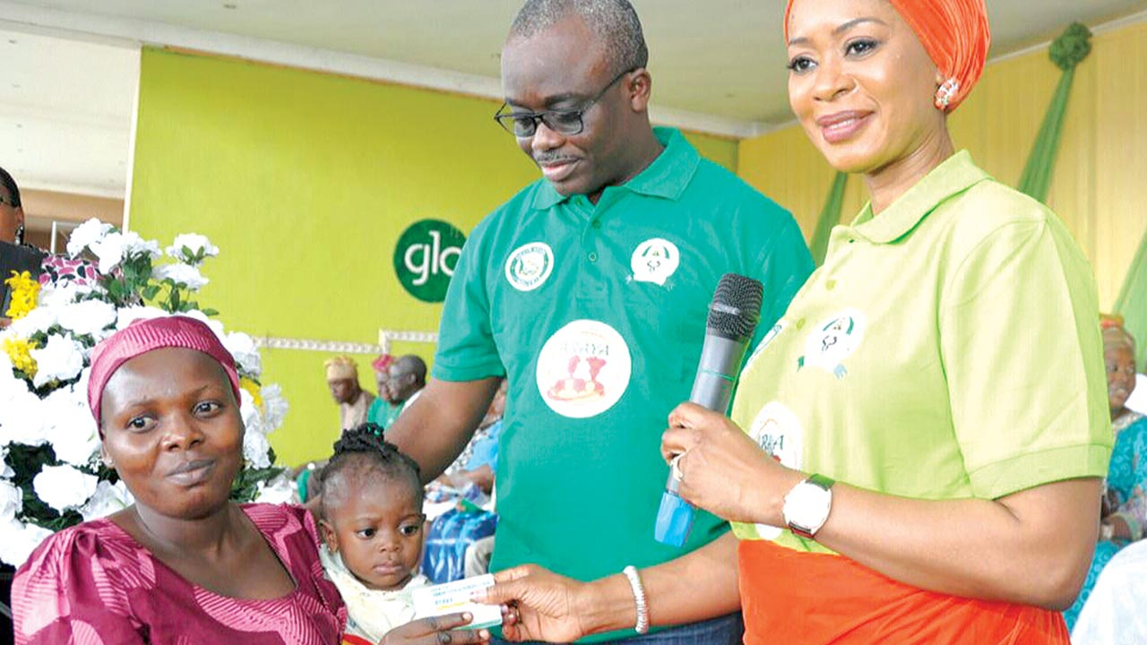 Wife of the governor of Ogun State, Mrs. Olufunso Amosun (right), handing over an Araya Card to Mrs. Oso Oyinkansola, while the State Commissioner for Health, Dr. Babatunde Ipaye looks on during the launch of the State Community Health Insurance Cards (Araya Card)