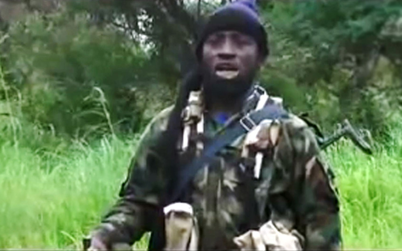 "This screengrab taken on August 8, 2016 from a Boko Haram video released by the Nigerian Islamist extremist group Boko Haram and obtained by AFP shows Boko Haram's shadowy leader Abubakar Shekau as he appeares in a new video vowing to fight on, shrugging off an apparent split in the hardline jihadist group blamed for thousands of deaths since 2009. ""I... Abubakar Ash-Shakawy (Shekau), the leader of Jama'atu Ahlissunnah Lidda'awati Wal Jihad, made it a duty for myself (to fight) Nigeria and the whole world,"" Shekau said in the video released on August 7, 2016, using the group's name since it declared allegiance to the so-called Islamic State. / AFP PHOTO / BOKO HARAM AND AFP PHOTO / HO"