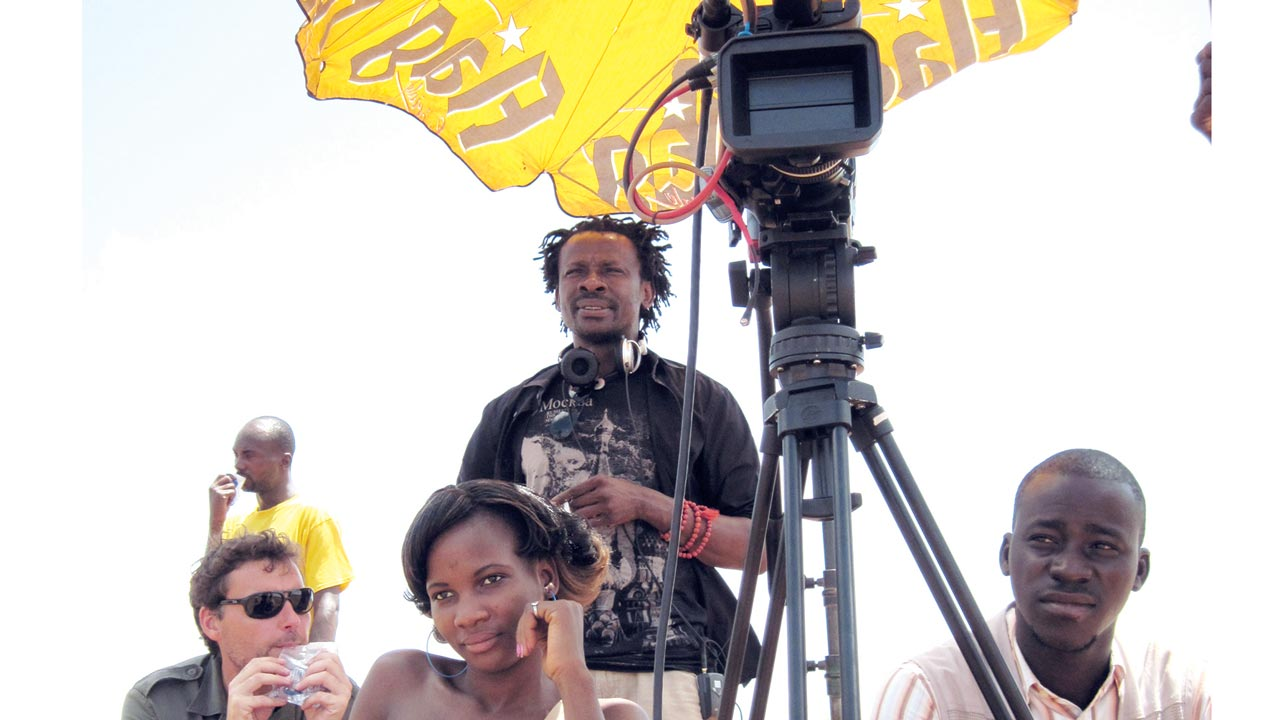 Aduaka (standing behind) on location with his crew.