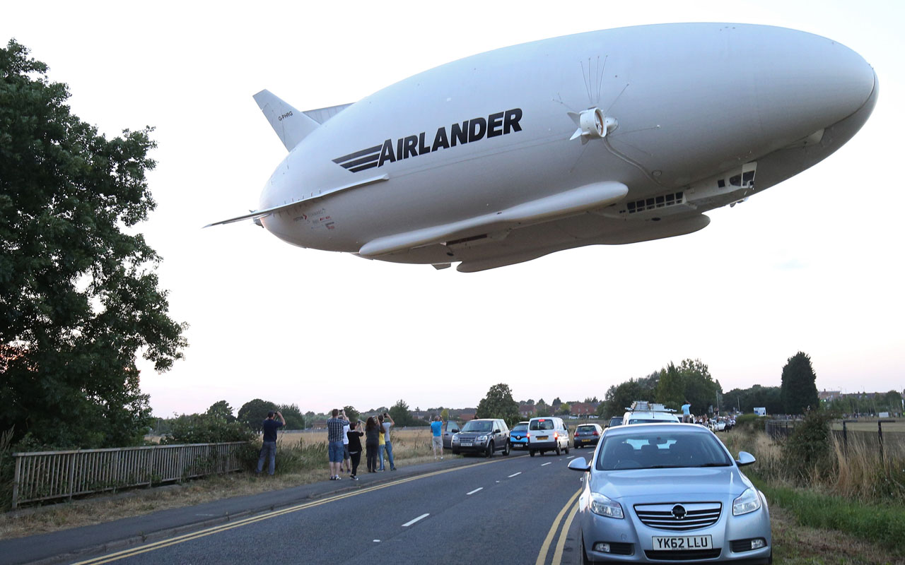(FILES) This file photo taken on August 17, 2016 shows the Hybrid Air Vehicles HAV 304 Airlander 10 hybrid airship in the air over a road on its maiden flight from Cardington Airfield near Bedford, north of London.  The world's largest aircraft suffered cockpit damage on Wednesday after nosediving while landing on its second test-flight, but there were no injuries, according to the craft's manufacturer.  / AFP PHOTO / JUSTIN TALLIS