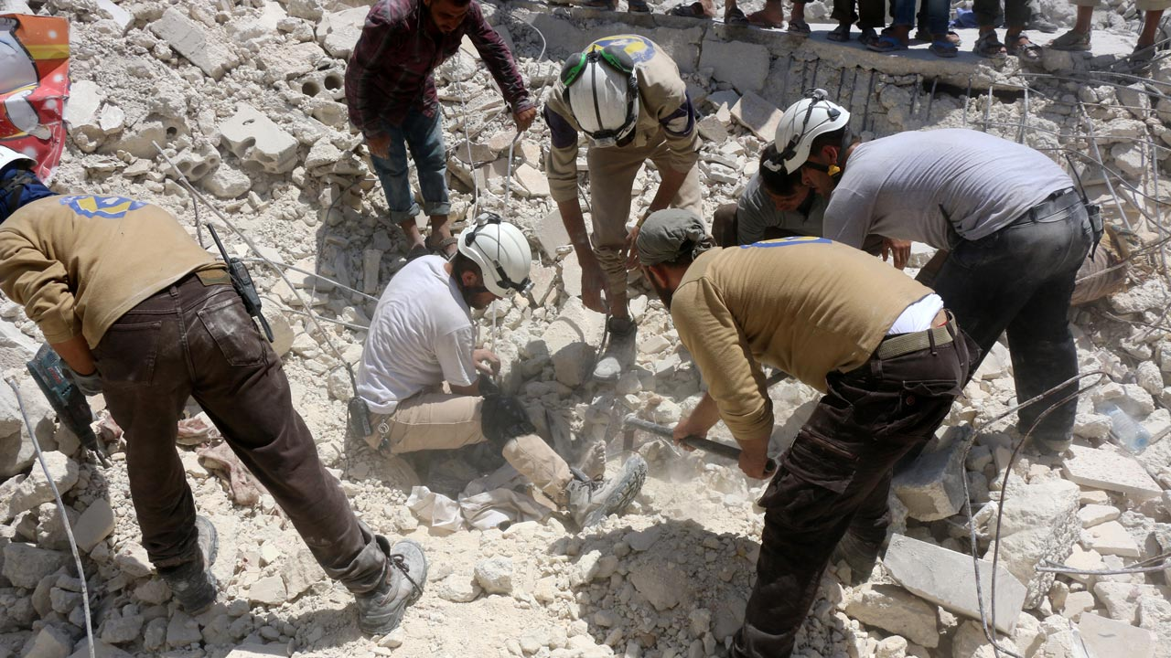 Syrian civil defence workers look for survivors under the rubble of a collapsed building following reported air strikes on July 17, 2016 in the rebel-controlled neighbourhood of Karm Homad in the northern city of Aleppo. Opposition-controlled parts of Syria's battered northern city Aleppo came under total siege, after government forces severed the last route out of the east. An estimated 300,000 civilians live in rebel-held neighbourhoods of Syria's second city, according to the United Nations, and there are fears that they could face starvation. THAER MOHAMMED / AFP
