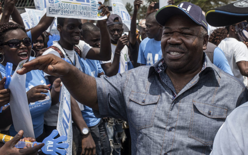 Incumbent  Gabonese President Ali Bongo Ondimba greets supporters as he arrives at a public gathering in Moanda on August 23, 2016. The one round presidential elections in Gabon to be held on August 27, 2016, will oppose Gabonese President Ali Bongo Ondimba to the former president of the Commission of the African Union Jean Ping, who rallied two other heavyweights of politics. / AFP PHOTO / MARCO LONGARI