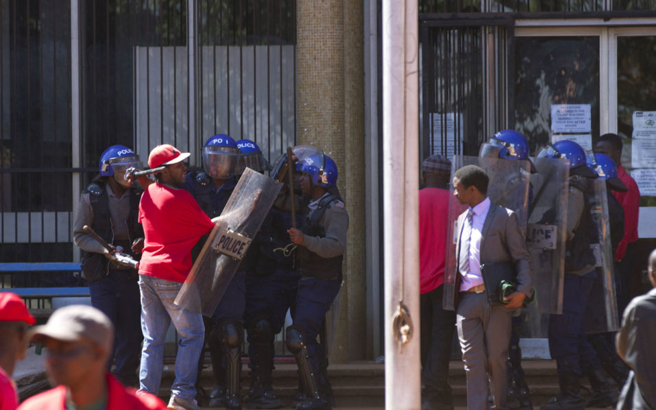 Riot police forces detain a man outside the High Court in Harare on August 26, 2016, during an opposition rally to demand electoral reforms. Riot police in Zimbabwe fired tear gas, beat up protesters and blocked off the site of an opposition rally in Harare on August 26, 2016, the latest in a string of demonstrations to hit the country. The rally -- which was authorised by a court -- was to demand electoral reforms before 2018 when 92-year-old President Robert Mugabe, who has ruled the southern African country for decades, will seek re-election. / AFP PHOTO / ZINYANGE AUNTONY