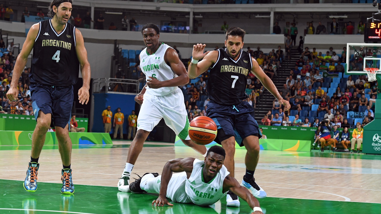 Nigeria's point guard Ben Uzoh (Bottom) falls next to Argentina's point guard Facundo Campazzo (R) during a Men's round Group B basketball match between Nigeria and Argentina at the Carioca Arena 1 in Rio de Janeiro on August 7, 2016 during the Rio 2016 Olympic Games. / AFP PHOTO / Mark RALSTON