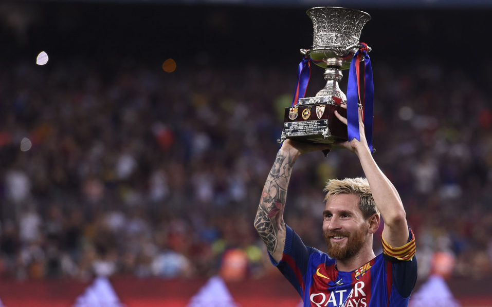 Barcelona's Argentinian forward Lionel Messi holds the Spanish Supercup trophy after winning  after winning the second leg of the Spanish Supercup football match between FC Barcelona and Sevilla FC at the Camp Nou stadium in Barcelona on August 17, 2016. / AFP PHOTO / JOSEP LAGO