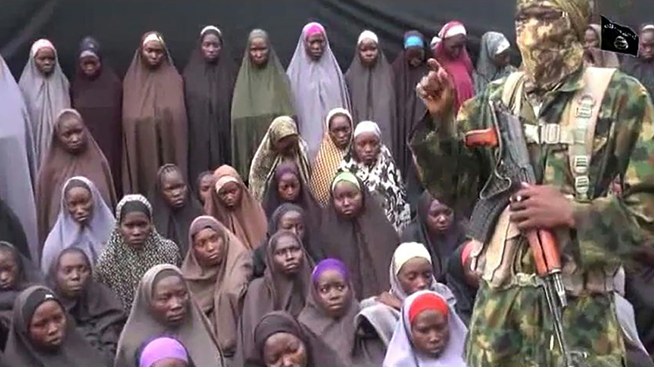This video grab image created on August 14, 2016 taken from a video released on youtube purportedly by Islamist group Boko Haram showing what is claimed to be one of the groups fighters at an undisclosed location standing in front of girls allegedly kidnapped from Chibok in April 2014. Boko Haram on August 14, 2016 released a video of the girls allegedly kidnapped from Chibok in April 2014, showing some who are still alive and claiming others died in air strikes. The video is the latest release from embattled Boko Haram leader Abubakar Shekau, who earlier this month denied claims that he had been replaced as the leader of the jihadist group. PHOTO: AFP / BOKO HARAM