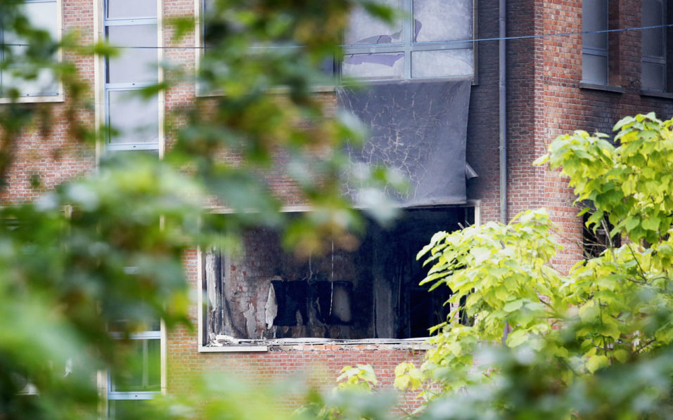 """A picture shows a damaged window of the National Institute for Criminalistics and Criminology (INCC-NICC) after an explosion overnight on August 29, 2016 in Neder-Over-Heembeek.  An explosion """"of criminal origin"""" at Belgium's national criminology institute in Brussels early Monday caused a fire and major damage but no casualties, officials said. Belgian media said the blast was caused by a car which rammed the building. It comes as Belgium remains on high alert following the devastating Islamic State-claimed suicide attacks on the city's airport and metro in March.  / AFP PHOTO / BELGA / THIERRY ROGE / Belgium OUT"""