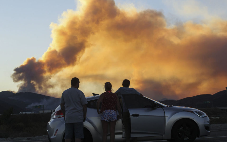 People watch the so-called Blue Cut wildfire in Lytle Creek, California, August 16, 2016.  The fire is currently 9,000 plus acres, with 700 personnel on scene. Fifty-seven engines, 8 crews, 8 air tankers, 2 Very Large Air Tankers (VLATS), with additional firefighters and equipment on order. There is imminent threat to public safety, rail traffic and structures. With this being a very quickly growing wildfire, evacuation instructions have been issued. An estimated 34,500 homes and 82,640 people are being affected by the evacuation warnings.  / AFP PHOTO / RINGO CHIU