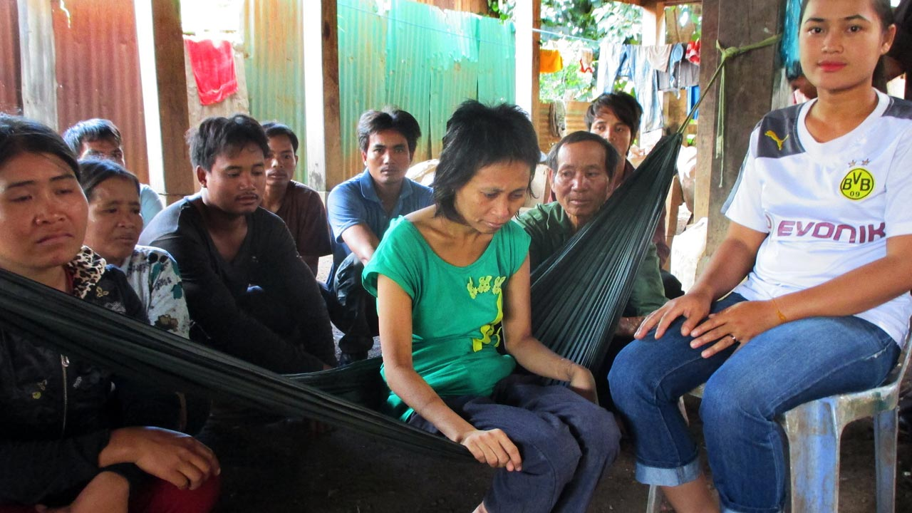 "This file photo taken on July 30, 2016 shows a handout photo released by the Cambodian Human Rights and Development Association (ADHOC)on August 1, 2016 showing ""jungle girl"" Rochom P'ngieng (C) sitting on a hammock as a Vietnamese man who claims to be her real father (C-R) sits behind her at a village in Rattanak Kiri province. A woman who has been staying with a Cambodian family ever since she emerged from the jungle a decade ago was returned to her real father in Vietnam on August 13, her adoptive family said.  CHHAY THI / ADHOC / AFP"