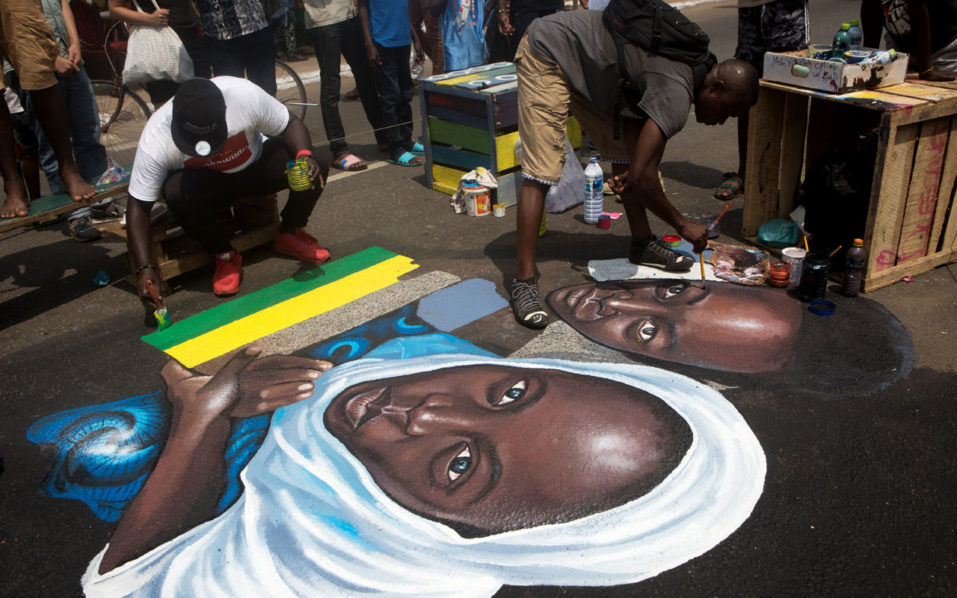 Artists perform a painting during the Chale Wote street art festival in Accra, on August 21, 2016. Some 200 african artists display their work from August 18 to 21, 2016, in the Ghanaian capital. / AFP PHOTO / Ruth McDowall