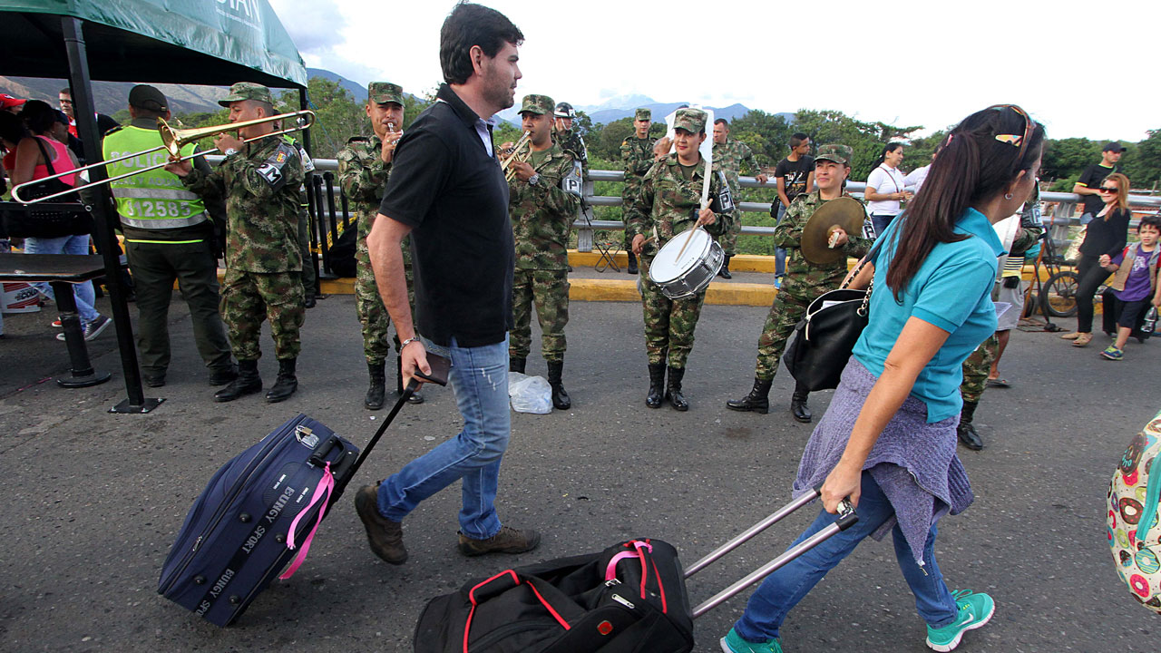 """Venezuelans walk by Colombian soldiers as they cross the border from San Antonio del Tachira, Venezuela, to Cucuta, Colombia on August 13, 2016. Venezuela and Colombia on Saturday opened several """"provisional"""" border crossing points for pedestrians for the first time in nearly a year as part of a progressive reopening agreed this week. GEORGE CASTELLANO / AFP"""