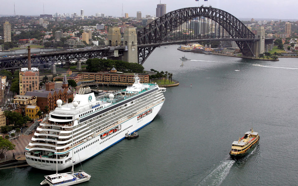 """(FILES) This file photo taken on February 16, 2005 shows the cruise liner """"Crystal Serenity"""" sits berthed at Sydney's historic Rocks area (L), with the Harbour Bridge (top).  Giant cruise ship heads to Arctic on pioneering journey. The Crystal Serenity, which set off from Seward, Alaska on August 16 with nearly 1,000 passengers, is scheduled to dock in New York on September 17. / AFP PHOTO / Greg Wood"""