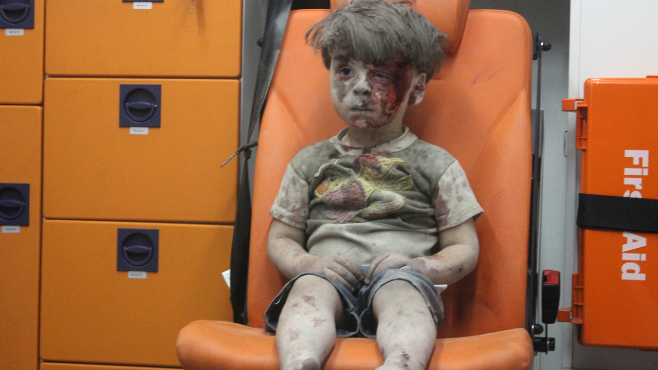 Omran, a four-year-old Syrian boy covered in dust and blood, sits in an ambulance after being rescued from the rubble of a building hit by an air strike in the rebel-held Qaterji neighbourhood of the northern Syrian city of Aleppo late on August 17, 2016. PHOTO: AFP / MAHMOUD RSLAN