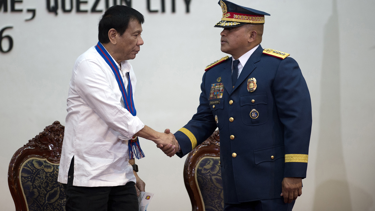 Philippine President Rodrigo Duterte (L) shakes hands with Philippine National Police (PNP) director General Ronal Dela Rosa during the 115th Police Service Anniversary at the Philippine National Police (PNP) headquarters in Manila on August 17, 2016. Philippine President Rodrigo Duterte lashed out at the United Nations for criticising the growing number of killings under his anti-drug campaign, warning foreign human rights probers against coming to his country. NOEL CELIS / AFP POOL / AFP