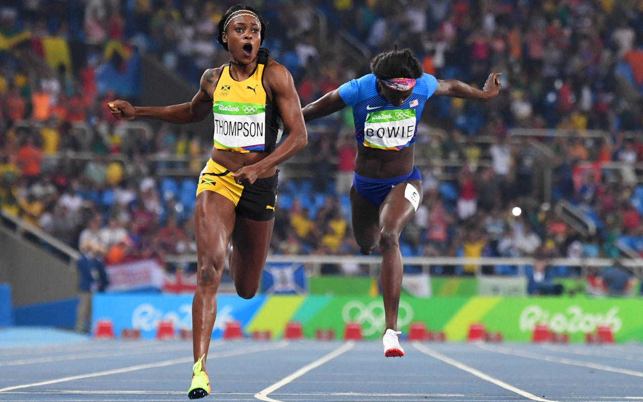 Jamaica's Elaine Thompson (L) reacts as she crosses the finish line next to bronze medallist USA's Tori Bowie to win the Women's 200m Final during the athletics event at the Rio 2016 Olympic Games at the Olympic Stadium in Rio de Janeiro on August 17, 2016. / AFP PHOTO / OLIVIER MORIN