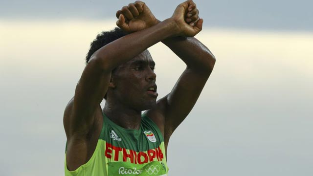 "Feyisa Lilesa in the ""x"" symbol is used in protests against the Ethiopian government attempts to reallocate land. Photo: BBC Sports"