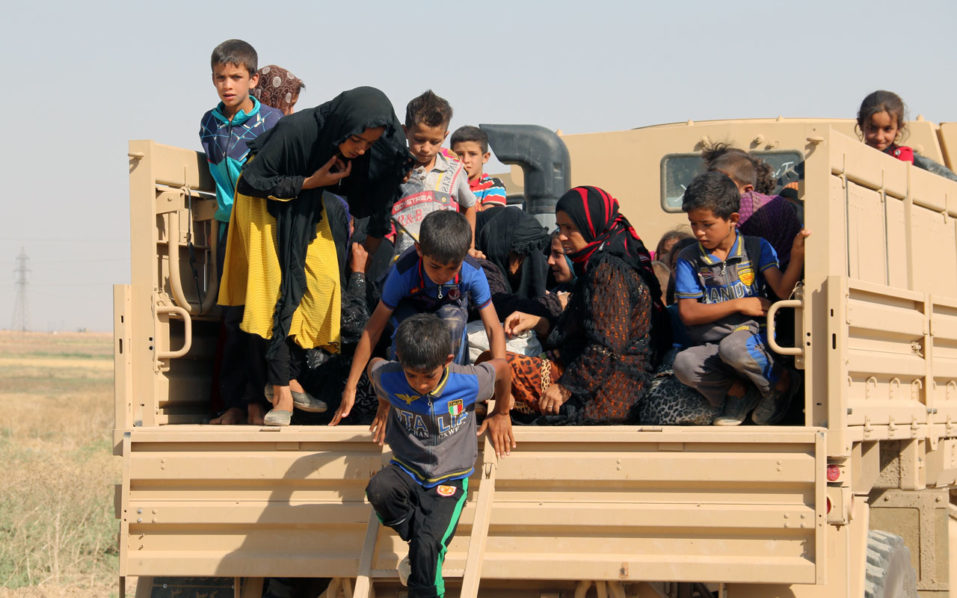Iraqi displaced families step down from a truck upon their arrival in an area controlled by the Peshmerga forces, some 55 kilometres west of Iraqi city of Kirkuk, on August 21, 2016 after they left their northern village of Hawija to escape from Islamic State (IS) group jihadists. / AFP PHOTO / Marwan IBRAHIM