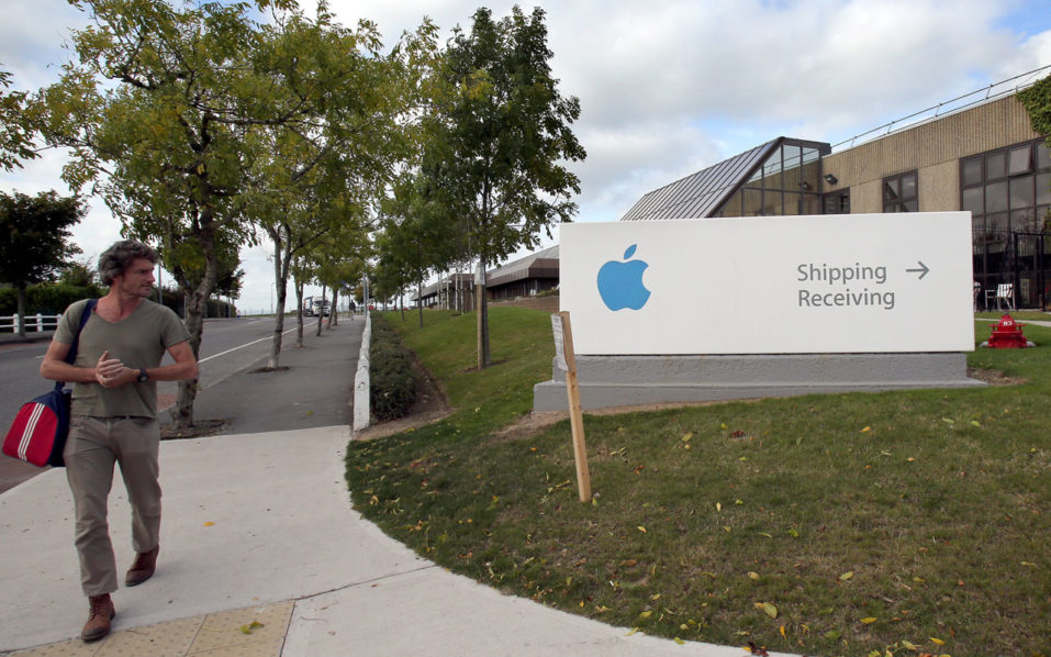 "(FILES) This file photo taken on October 2, 2014 shows a man passing by buildings on The Apple campus in Cork, southern Ireland. The European Union on August 30, 2016, said US tech giant Apple must repay a record 13 billion euros ($14.3 billion) in back taxes after ruling that a series of Irish sweetheart tax deals were illegal. ""The European Commission has concluded that Ireland granted undue tax benefits of up to 13 billion euros to Apple. This is illegal under EU state aid rules because it allowed Apple to pay substantially less tax than other businesses. Ireland must now recover the illegal aid,"" a Commission statement said. / AFP PHOTO / PAUL FAITH"