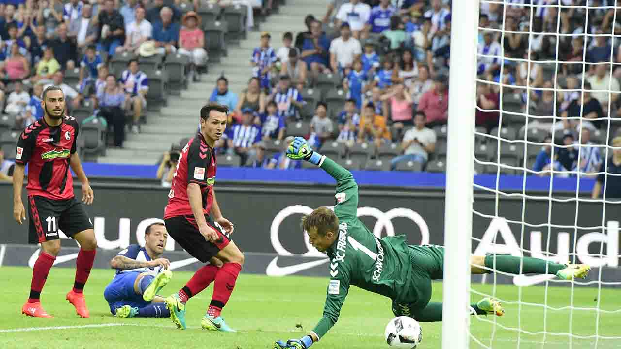 Berlin's forward Julian Schieber (2nd L) scores against Freiburg's midfielder Nicolas Hoefler (2nd R), Freiburg's midfielder Onur Bulut (L) and Freiburg's goalkeeper Alexander Schwolow (R) during the German first division Bundesliga football match of Hertha BSC Berlin vs SC Freiburg in Berlin, Germany, on August 28, 2016. / AFP PHOTO / TOBIAS SCHWARZ / RESTRICTIONS: DURING MATCH TIME: DFL RULES TO LIMIT THE ONLINE USAGE TO 15 PICTURES PER MATCH AND FORBID IMAGE SEQUENCES TO SIMULATE VIDEO. == RESTRICTED TO EDITORIAL USE == FOR FURTHER QUERIES PLEASE CONTACT DFL DIRECTLY AT + 49 69 650050
