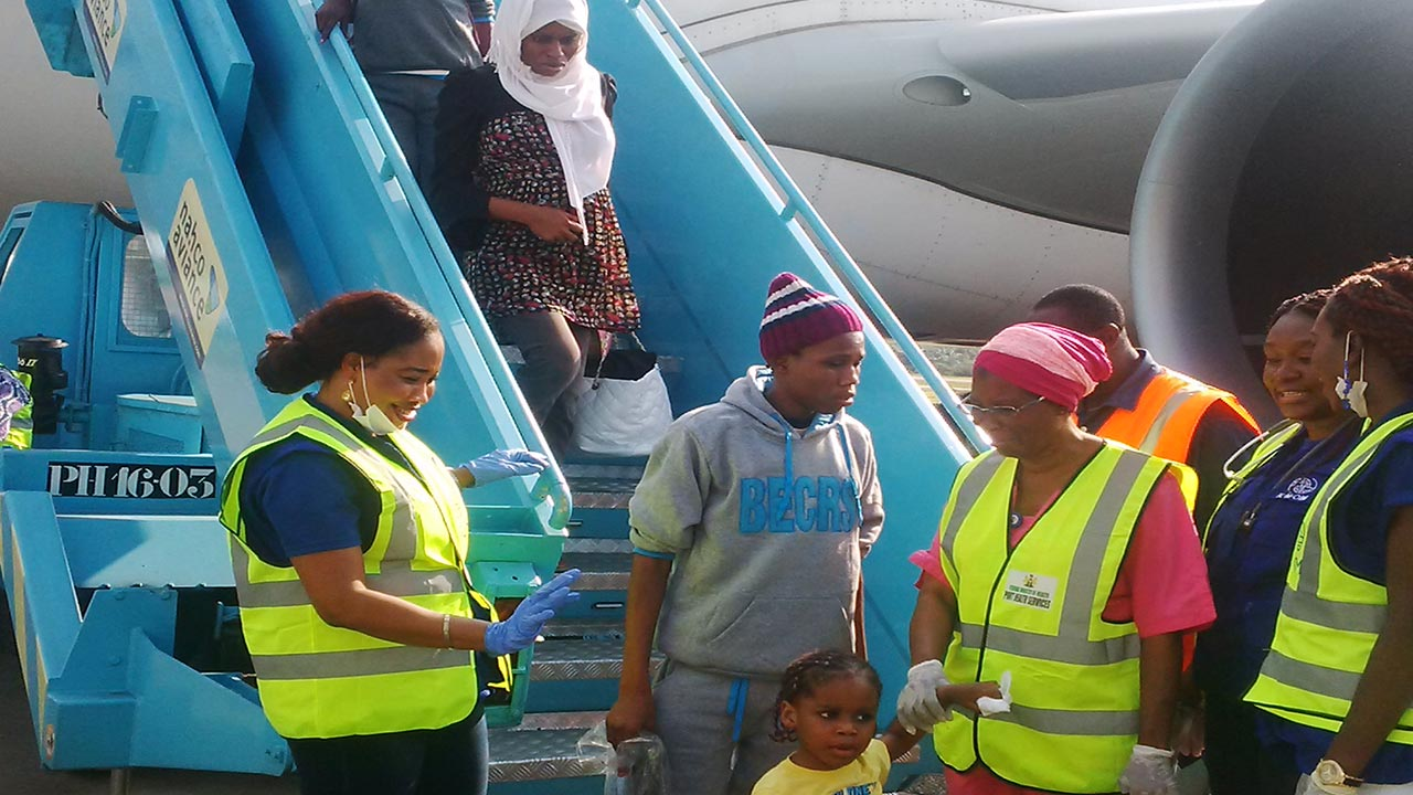 Some Nigerian deportees from Libya alighting from the plane at Murtala Mohammed International Airport Lagos recently.  (Insert) Some African illegal migrants in a boat on the Mediterranean sea heading to Europe from southern Libya  PHOTO: CNN