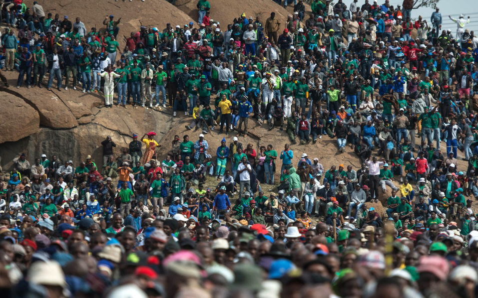 (FILES) This file photo taken on August 16, 2016 shows  Miners gather during a rally on the fourth anniversary of the Marikana Massacre, where 34 striking miners were killed by police, on August 16, 2016 in Rustenburg, South Africa.  The South African government is ready to pay out compensation to victims of a 2012 police shooting that left 34 mineworkers dead and dozens wounded, the presidency said on August 18, 2016. The miners were gunned down after police were deployed to break up a wildcat strike that had turned violent at the Lonmin-owned Marikana platinum mine northwest of Johannesburg in August 2012. / AFP PHOTO / MUJAHID SAFODIEN