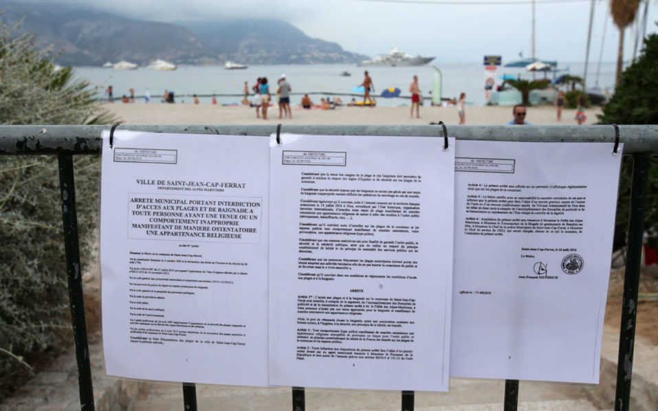 """This picture taken on August 19, 2016 shows the bylaw forbidding women to wear Burkini at the main beach of Saint-Jean Cap Ferrat, southeastern France. Nice has become the latest French seaside resort to ban the burkini, the body-concealing Islamic swimsuit that has sparked heated debate in secular France. Using language similar to bans imposed in a string of other towns on the French Riviera, the city barred apparel that """"overtly manifests adherence to a religion at a time when France and places of worship are the target of terrorist attacks"""".  / AFP PHOTO / JEAN CHRISTOPHE MAGNENET"""