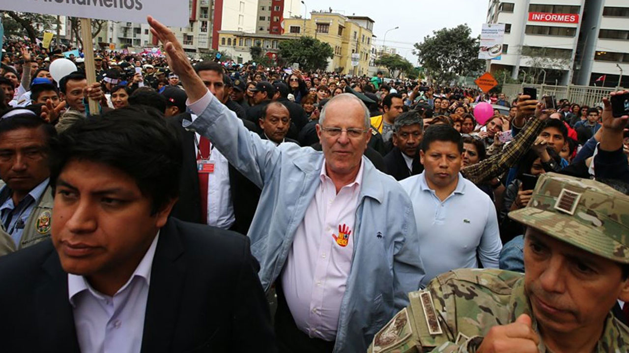 """A handout picture released by the Peruvian national news agency ANDINA shows President Pedro Pablo Kuczynski participating with thousands of demonstrators in the """"Ni una menos"""" (Not One Less) march through the center of Lima to the palace of justice holding banners and posters condemning gender violence and femicide - gender-based killings - on August 13, 2016. HO STR / ANDINA / AFP"""