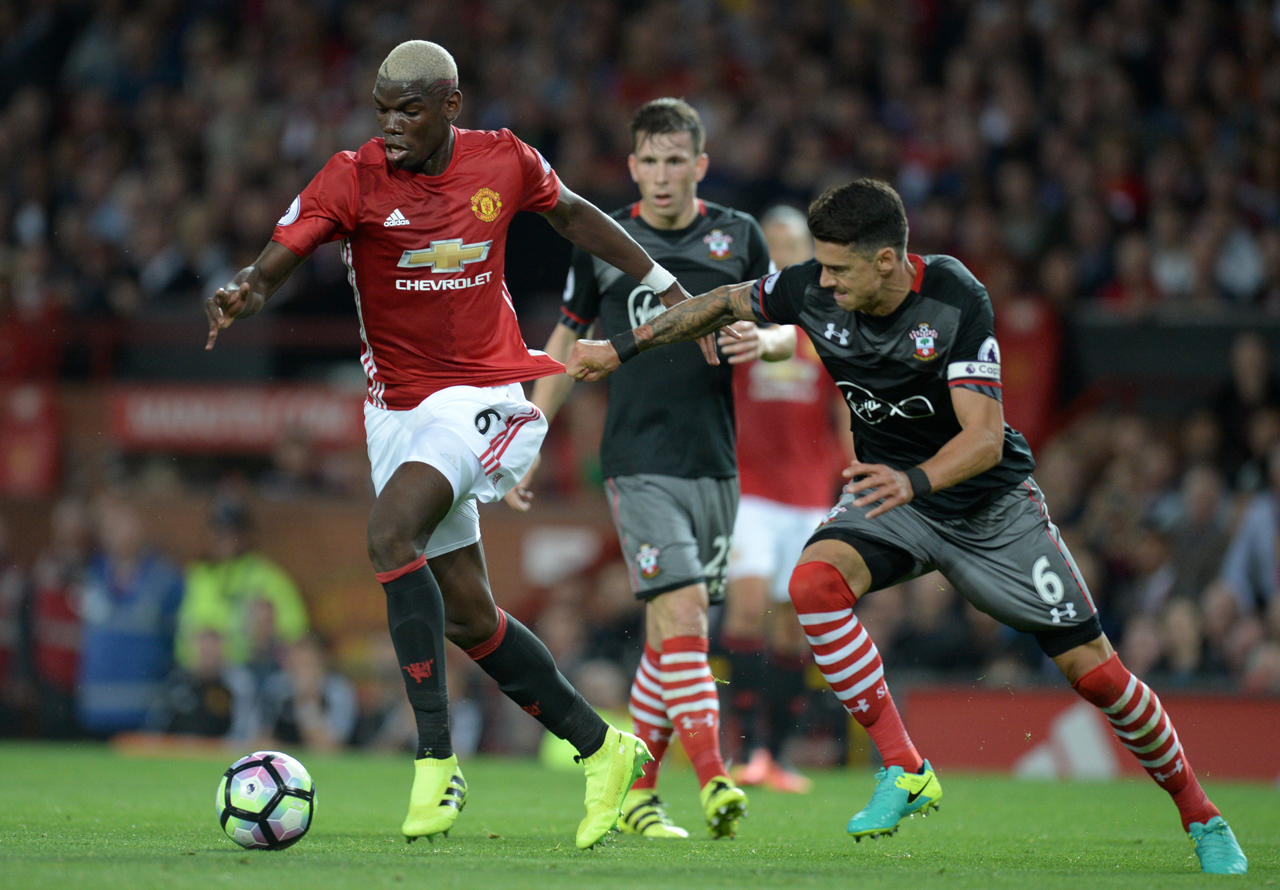 Manchester United's French midfielder Paul Pogba (L) vies with Southampton's Portuguese defender Jose Fonte (R) during the English Premier League football match between Manchester United and Southampton at Old Trafford in Manchester, north west England, on August 19, 2016. Oli SCARFF / AFP
