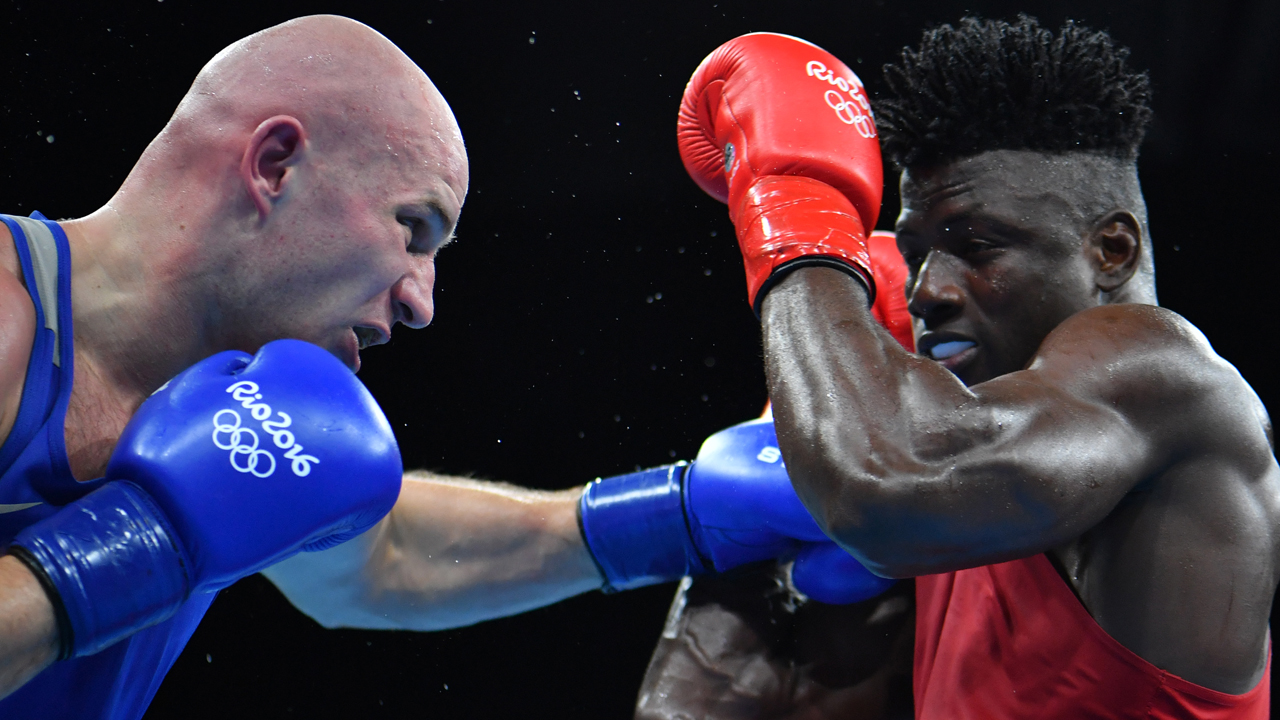 Nigeria's Efe Ajagba (R) is punched by Kazakhstan's Ivan Dychko during the Men's Light Welter (64kg) Quarterfinal 4 match at the Rio 2016 Olympic Games at the Riocentro - Pavilion 6 in Rio de Janeiro on August 16, 2016.   / AFP PHOTO / Yuri CORTEZ