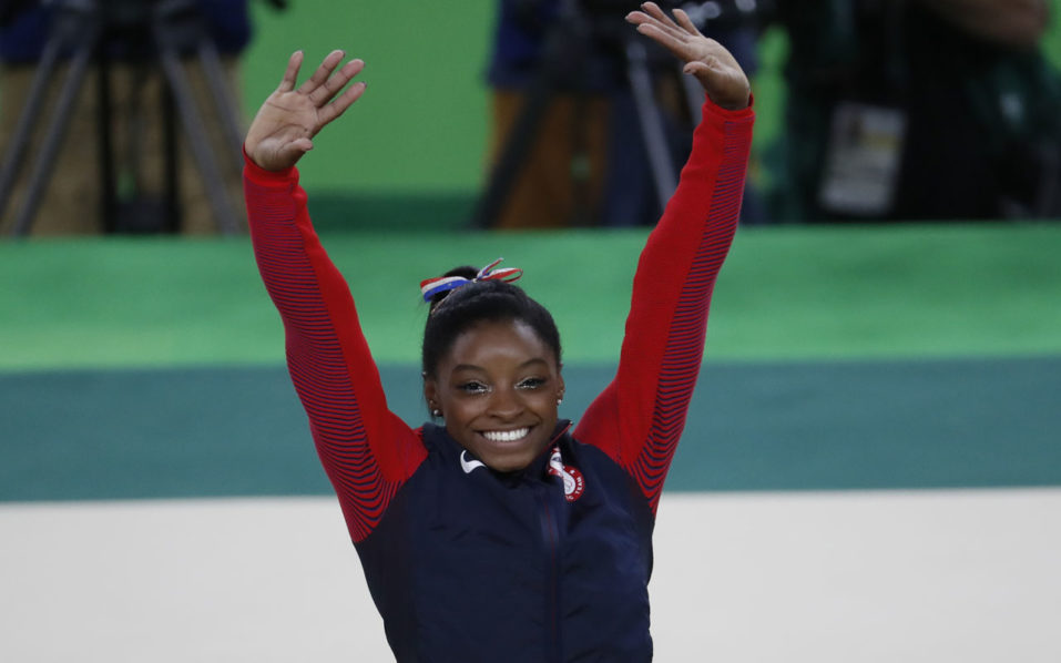 US gymnast Simone Biles celebrates on the podium of the women's floor event final of the Artistic Gymnastics at the Olympic Arena during the Rio 2016 Olympic Games in Rio de Janeiro on August 16, 2016. / AFP PHOTO / Thomas COEX