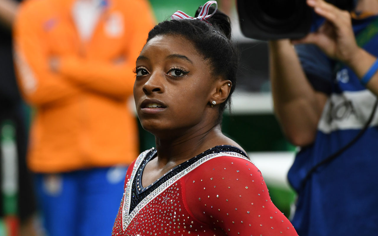 US gymnast Simone Biles reacts after competing in the women's balance beam event final of the Artistic Gymnastics at the Olympic Arena during the Rio 2016 Olympic Games in Rio de Janeiro on August 15, 2016. / AFP PHOTO / Toshifumi KITAMURA