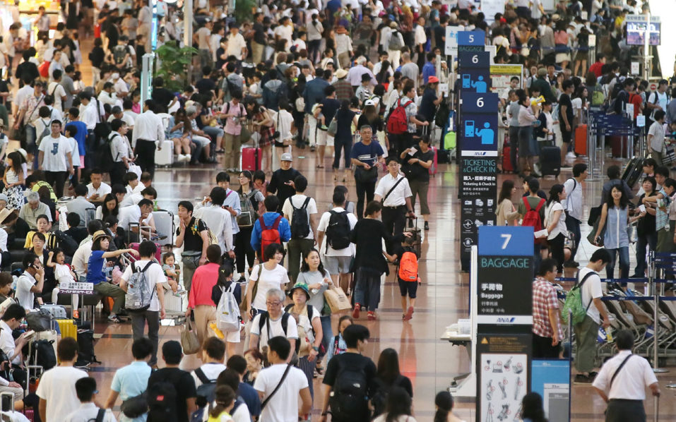 People crowd at the departure lobby at Haneda Airport in Tokyo on August 22, 2016.   A typhoon is on course for a direct hit on Tokyo, with nearly 400 flights grounded due to heavy rain and strong winds.     / AFP PHOTO / JIJI PRESS / STR / Japan OUT