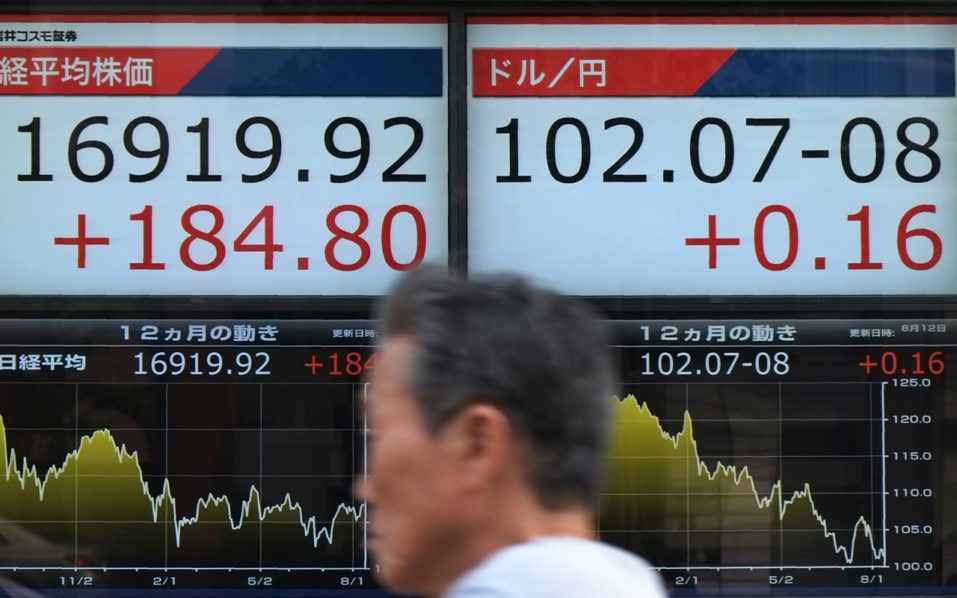 A man walks past electric quotation boards displaying share prices on the Tokyo Stock Exchange (L) and the foreign exchange rate between the yen and the US dollar (R) in Tokyo on August 12, 2016. Tokyo's benchmark index closed at its highest level in over two months on August 12 after Wall Street powered to fresh records and a weaker yen boosted sentiment. / AFP PHOTO / KAZUHIRO NOGI