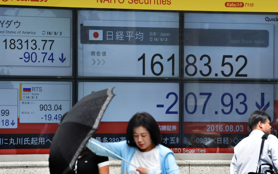 Pedestrians walk past an electric quotation board displaying the Nikkei key index of the Tokyo Stock Exchange in Tokyo on August 3, 2016. Tokyo stocks extended a sell-off on global markets at the open on August 3, with a stronger yen hitting exporters and investors shrugging off a huge government stimulus package. / AFP PHOTO / KAZUHIRO NOGI