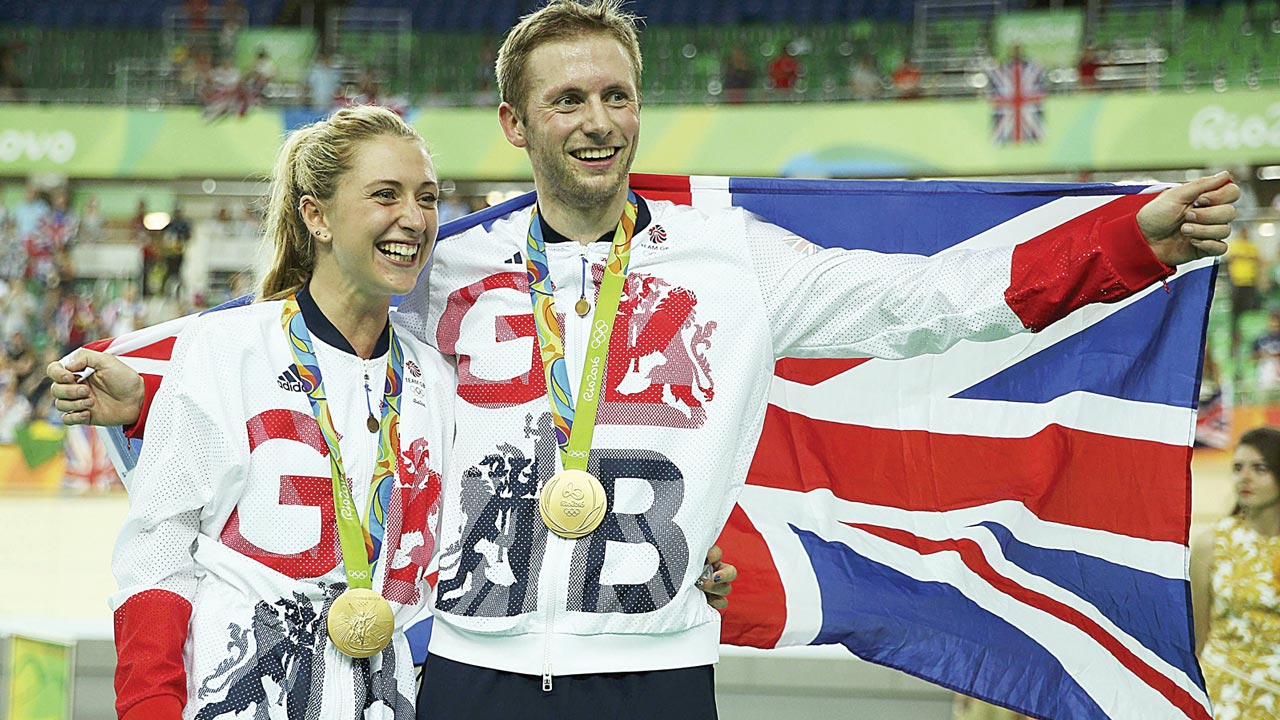 Trott and Kenny with British flag after receiving medals.