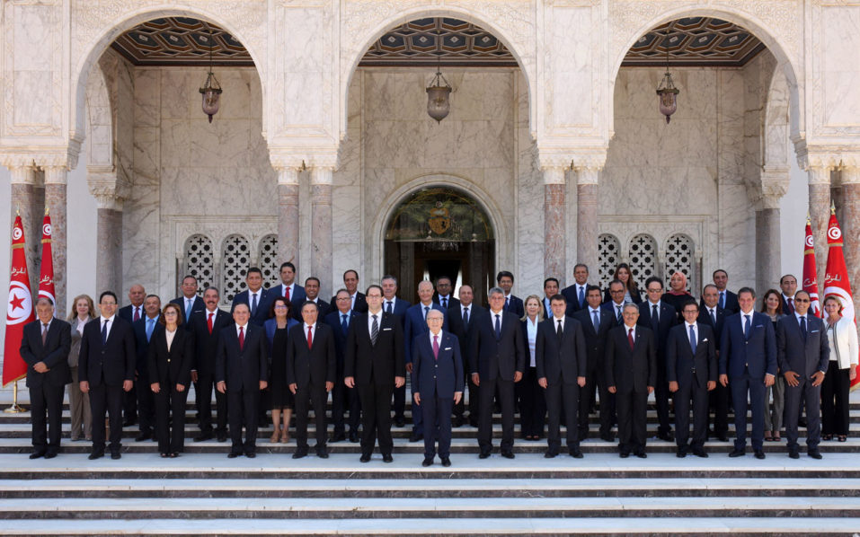 """A handout picture provided by the Tunisian Presidency Press Service on August 27, 2016, shows Tunisian President Beji Caid Essebsi (C-R) posing for an official picture with his new Prime Minister Youssef Chahed (C-L) and members of his cabinet after the new government swearing-in ceremony at Carthage Palace, near the capital Tunis. Tunisia's new Prime Minister Youssef Chahed and members of his cabinet were sworn in, the presidency said, after approval from parliament. The prime minister and his 26 ministers swore to """"work devotedly for the good of Tunisia"""" and to """"respect its constitution and laws"""", it said. / AFP PHOTO / TUNISIAN PRESIDENCY / HO /"""