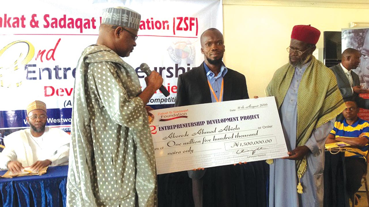 Chairman of the occasion, Ambassador Adamu Babagida Ibrahim (left) assisted by Sheikh Muhammad Jamiu Trimidhi to present a N1.5 million dummy check to overall male winner, Ahmad Akorede at the second Entrepreneurship Development Project organised by Zakat and Sadaqat Foundation (ZSF) in Lagos.