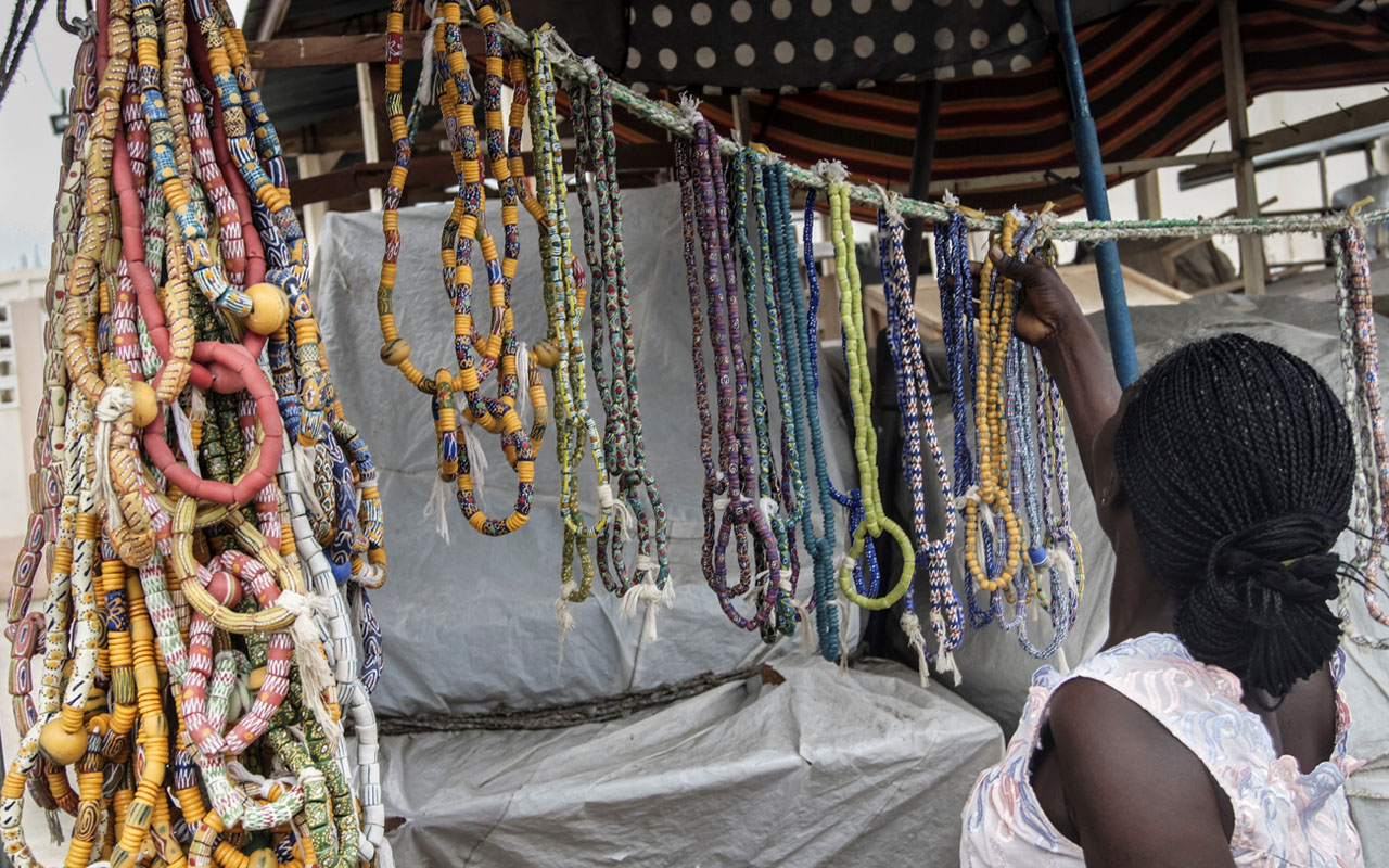 TO GO WITH AN AFP STORY BY EMILE KOUTON A Togolese woman looks at waist beads at a stall in Lome on July 20, 2016. In the Togo capital, the fashion for wearing strings of beads around the waist -- an ancient tradition known as 'djonou' in the Gulf of Guinea region -- has made a comeback in recent years. Favoured by young women as an object of both beauty and seduction, the djonou also has a spiritual aspect, guaranteeing the wearer the protection of her ancestors. Some say it can even cure pain in the kidneys.  / AFP PHOTO / EMILE KOUTON