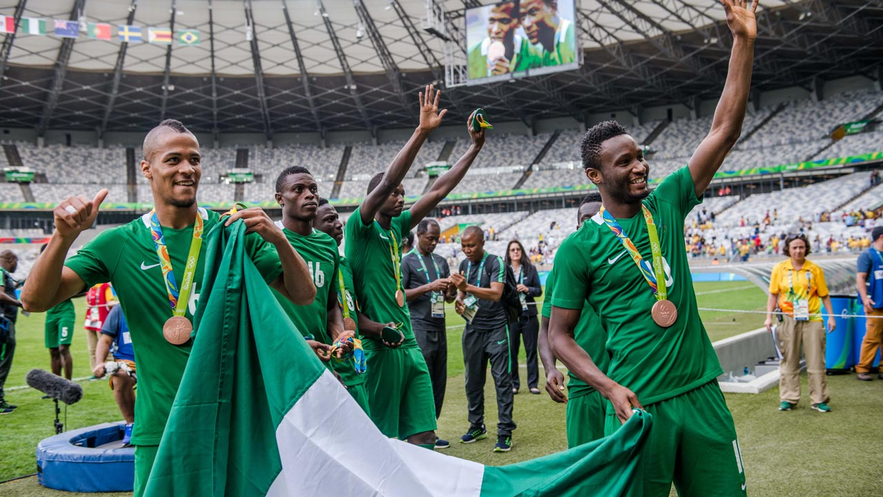 Nigeria's players William Ekong (L) and John Obi Mikel (R) celebrate after receiving their bronze medals during the medal ceremony after defeating Honduras in the Rio 2016 Olympic Games men's bronze medal football match at the Mineirao stadium in Belo Horizonte, Brazil, on August 20, 2016. GUSTAVO ANDRADE / AFP