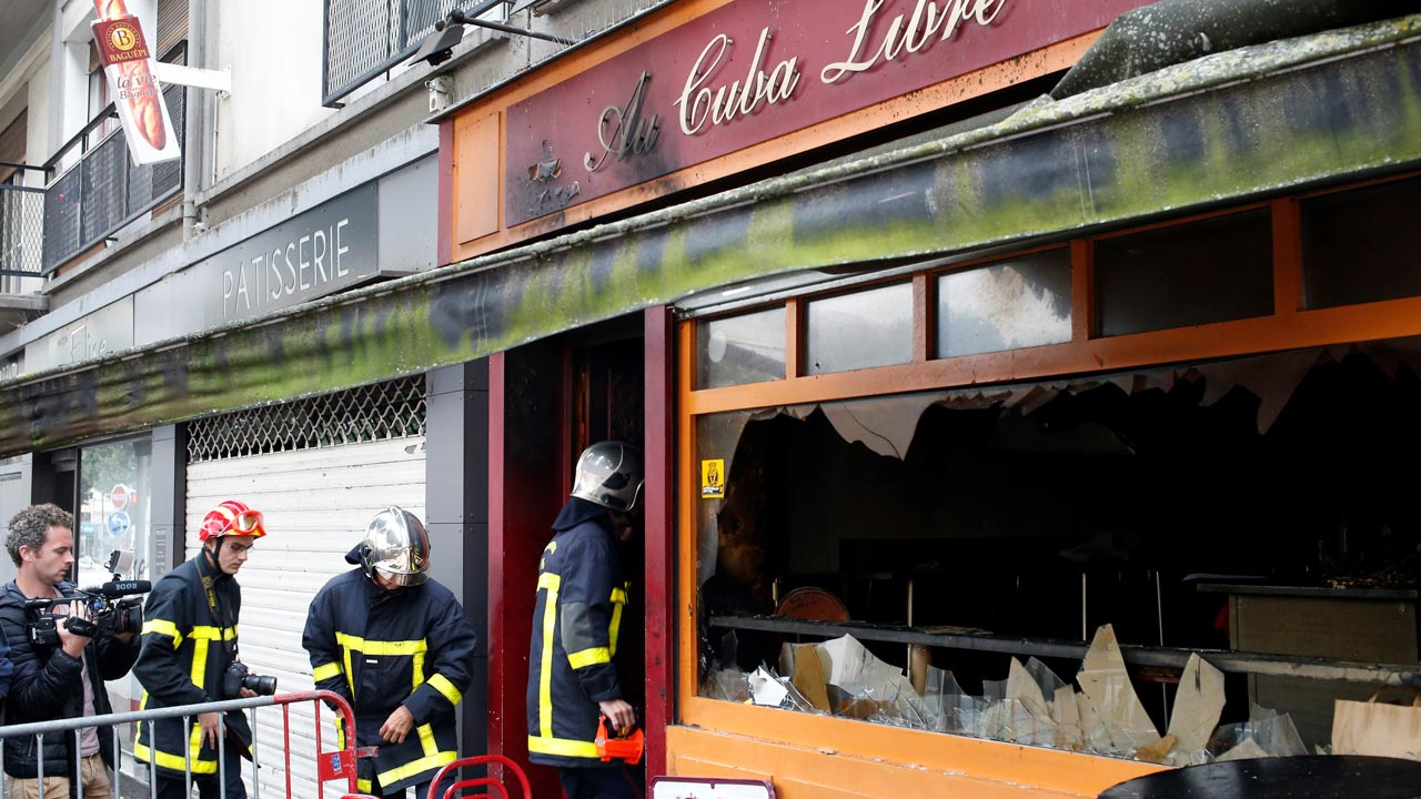 Firefighters enter the damaged Au Cuba Libre bar in Rouen, northern France, on August 6, 2016, after a fire broke out overnight in the bar during a birthday party. At least 13 people were killed and six injured in the fire, officials said. MATTHIEU ALEXANDRE / AFP