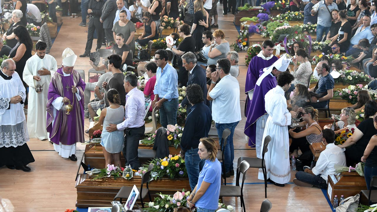 "People attend a funeral service for victims of the earthquake, at a gymnasium arranged in a chapel of rest on August 27, 2016, in Ascoli Piceno, three days after a 6.2-magnitude earthquake struck the region killing some 281 people. Flags flew at half mast across Italy on August 27, 2016 as the country observed a day of mourning for the victims of an earthquake that killed nearly 300 people. President Sergio Mattarella paid tribute to the ""extraordinary effort"" of more than 4,000 rescue experts and volunteers as he began what was set to be an emotionally charged day with a brief visit to Amatrice, around 100 kilometres (60 miles) northeast of Rome.The small mountain town suffered the heaviest losses in the disaster with around two thirds of the quake's 284 confirmed victims buried under tonnes of collapsed masonry in its devastated centre. PHOTO: ALBERTO PIZZOLI / AFP"