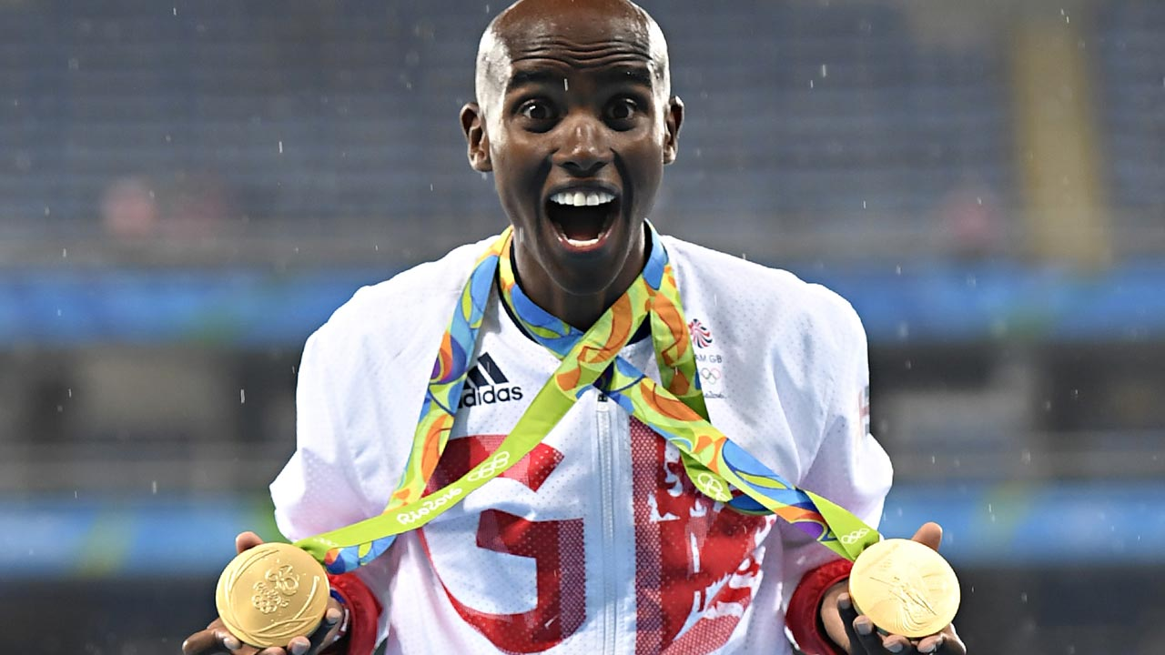 Gold medallist Britain's Mo Farah celebrates near the podium for the Men's 5000m during the athletics event at the Rio 2016 Olympic Games at the Olympic Stadium in Rio de Janeiro on August 20, 2016. PHOTO: Eric FEFERBERG / AFP